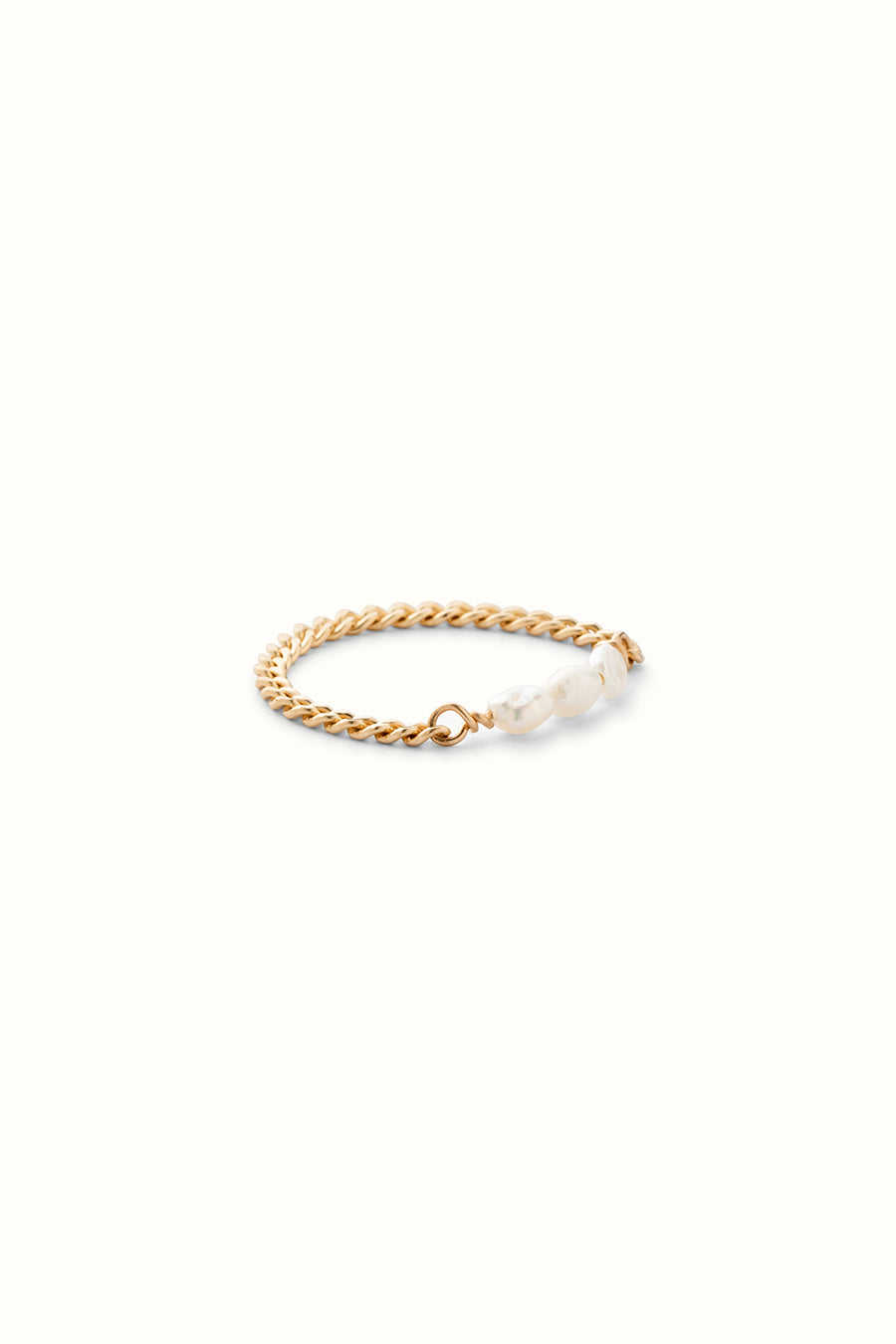 a fine curb chain ring with pearls on a white background