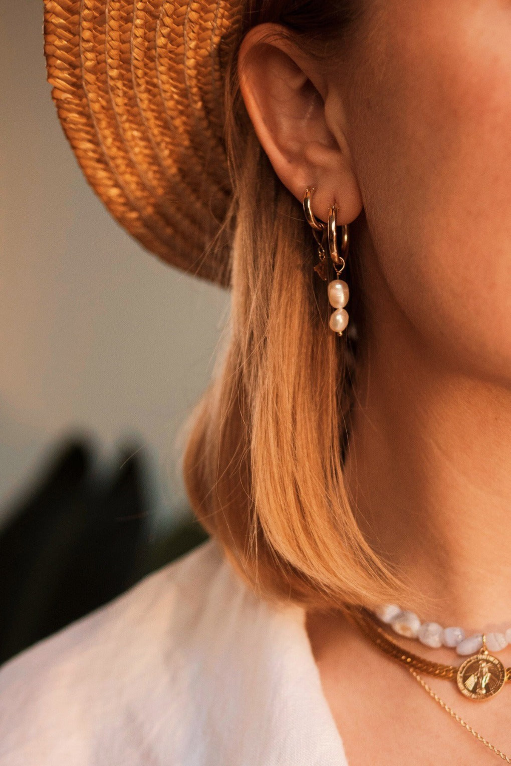 a set of gold filled and pearl drop hoop earrings worn by a model