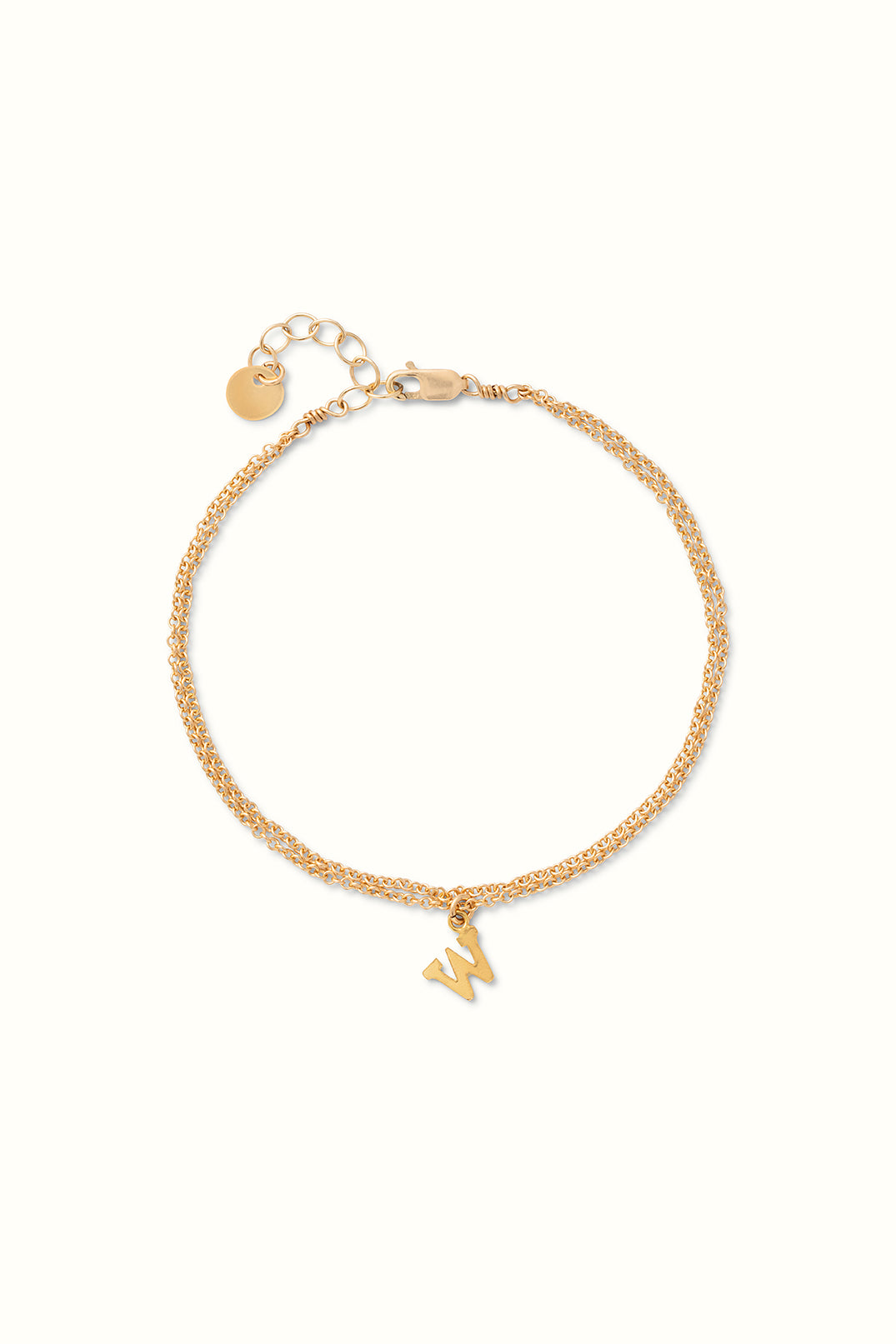 a close up of a gold filled initial chain bracelet on a white surface