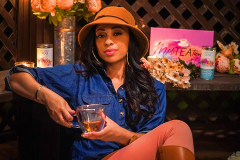 Founder Caryn Ward Ross sipping tea and displaying her MediTEAtions with Caryn tea collections