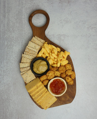 image of crackers placed between bowls and cheese on board