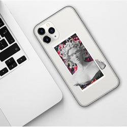 Clear iPhone case with a picture of a medusa statue on top of a pink floral background. The eyes and shoulders of the statue are staticky, showing a warped illusion.