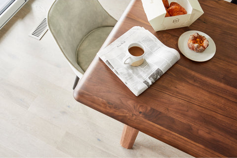 Malibu Dining Table, with a newspaper, coffee mug on top of it. Table made of Walnut. You also can see a beige comfortable chair.