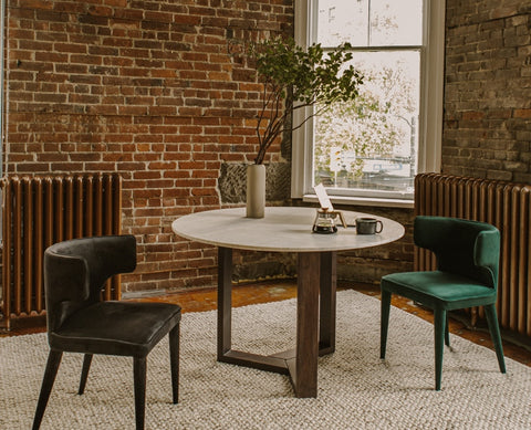 Jinxx Dining Table made of Satwaria marble and Acacia Wood Frame. Placed on a brick wall dining room with a black and a green comfortable dining chair.