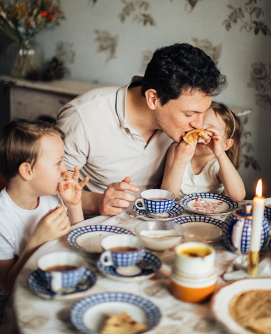 A man, dad with the kids eating on a dining table