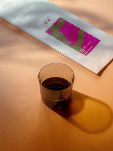 Coffee bag of Field Coffee Cherry Ripe Espresso Blend on table next to a cup of filter coffee