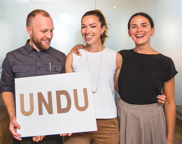 The 3 founders of Undu. Charlie, Katherine and Robin, holding a sign that says Undu. Smiling in the Dyson offices.