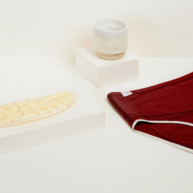 A display of The Period Collection Bundle. The Original Heat Pack on a presentation block, The Take It Easy Tumbler on a presentation block, and the Keep It Brief in Merlot (burgundy) on a white background.