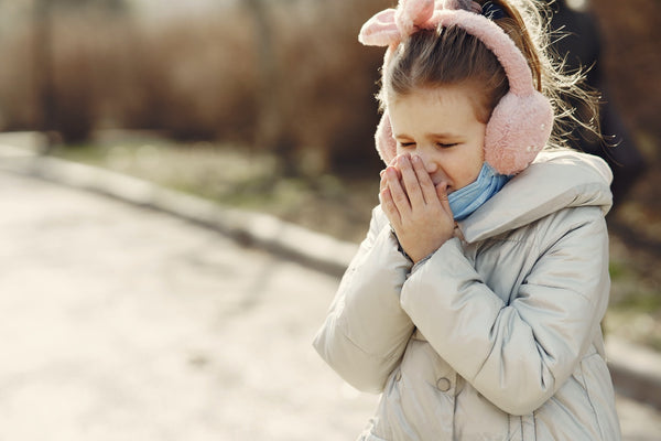 little girl sneezing and coughing outdoor during winter time