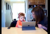 Image of little kid using tablet with woman