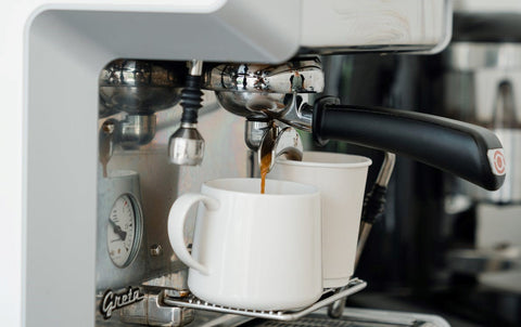 A coffee machine pouring coffee into a mug and cup
