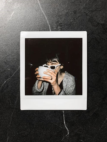 A Polaroid photo of a celebrity drinking coffee