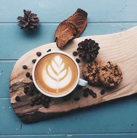 A charcuterie board with coffee, chocolate chip cookies, and fresh coffee beans online