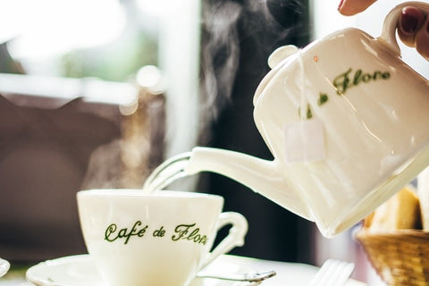 """coffee being poured in a cup labelled """"cafe de flora"""""""