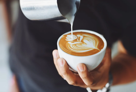 A man is holding a cup of coffee and pouring milk into it from a steel container