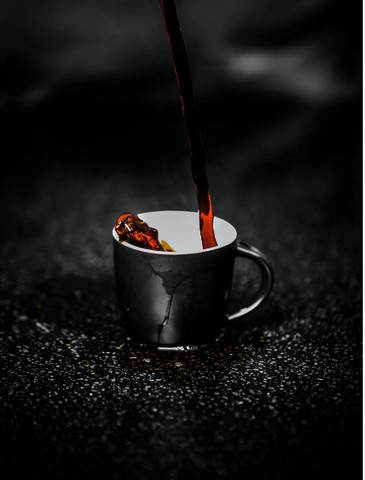 black coffee is being poured into a coffee mug