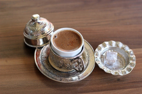 Traditional Turkish coffee in a cup with a sugar cube