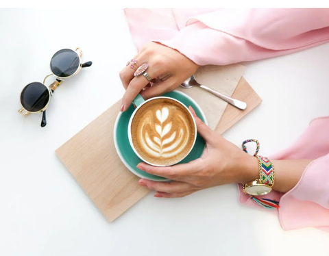 A woman is holding French vanilla coffee bought online on her charcuterie board with a spoon and tissue