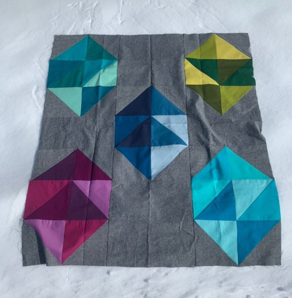 Facets modern gemstone quilt pattern by Monika Henry of Penny Spool Quilts - Quilt featuring modern, simplified gemstones in a variety of colours on grey background