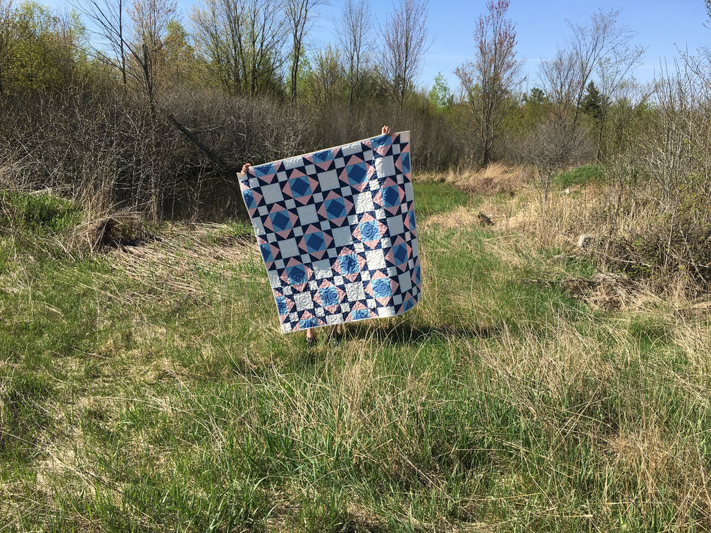 Victorian Tiles Quilt Pattern by Penny Spool Quilts - sample quilt in blue and pink being held up in a field of grass