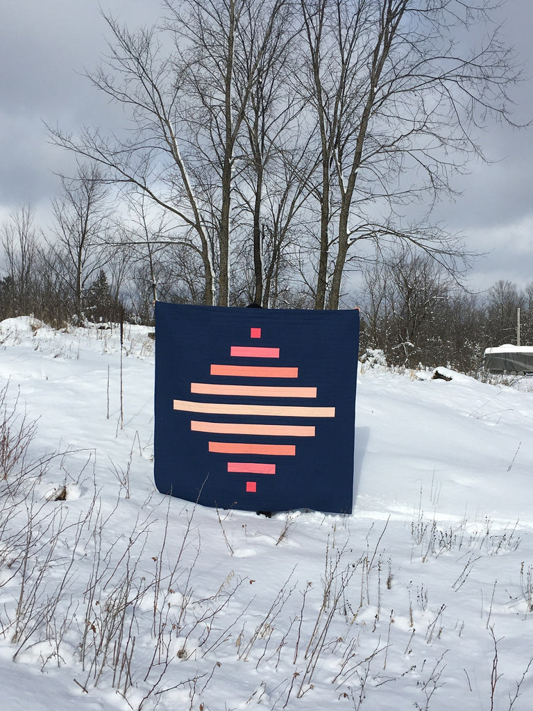 spinning top quilt by penny spool quilts, pink ombre kona cotton on navy background, outdoors in the snow