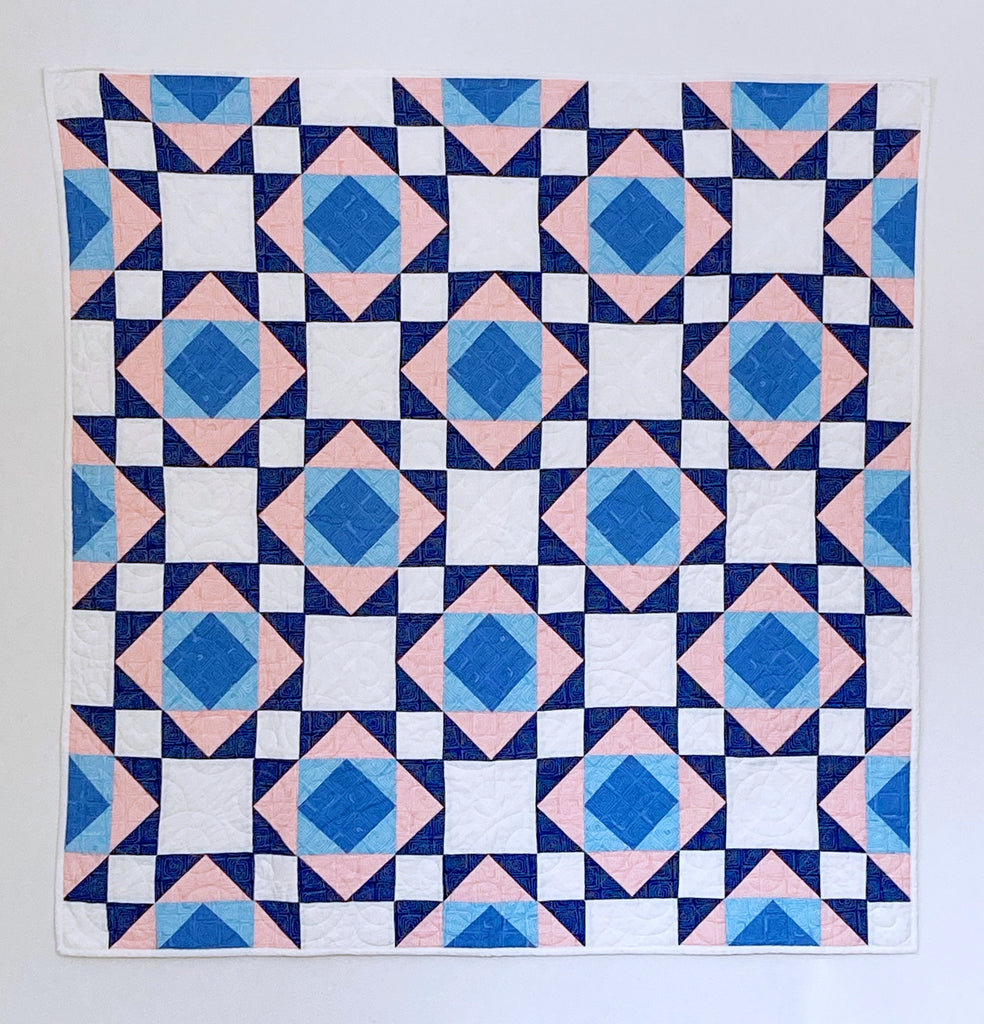 Victorian Tiles Quilt Pattern by Penny Spool Quilts - sample quilt in pink, blue and white on a white wall