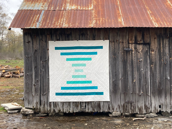 Raise The Bar modern quilt pattern by Penny Spool Quilts - turquoise ombre quilt on an old barn wall