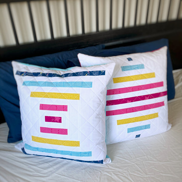 Raise the Bar beginner-friendly modern big block quilt pattern, courthouse steps quilt pattern by Penny Spool Quilts - pillow sample in pink, mustard and blue on white background