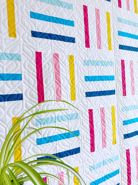 Bar Code quilt pattern by Monika Henry of Penny Spool Quilts - pink, yellow and blue bars on white background, square throw