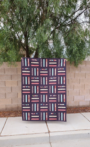 Bar Code Quilt pattern by Monika Henry of Penny Spool Quilts - tester quilt by Kristen Saffle with multicoloured stripes on purple