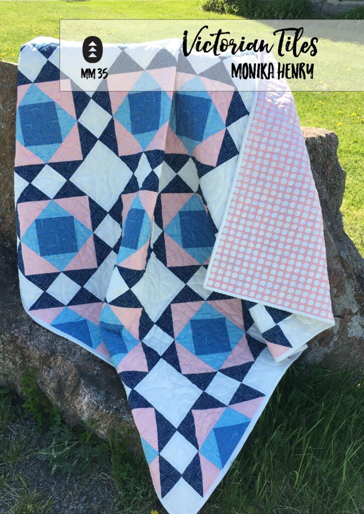 Victorian Tiles Quilt Pattern by Penny Spool Quilts - magazine pattern cover page with sample quilt in pink and blues draped over big rock