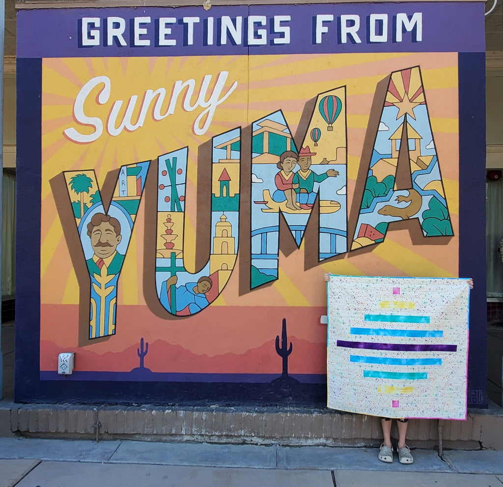 spinning top baby quilt shown in front of sign that says greetings from sunny yuma
