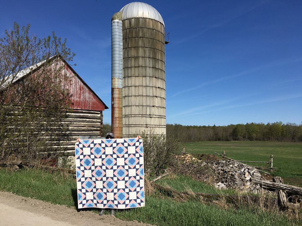 Victorian Tiles Quilt Pattern by Penny Spool Quilts - sample quilt in pink and blue being held up in front of a barn and silo