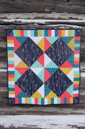 Canadian Diamond quilt pattern by Penny Spool Quilts, featuring four large diamonds surrounded by half-square triangles and a pieced border. Quilt shown in navy with pink, yellow, aqua and white accents, hanging from log wall.