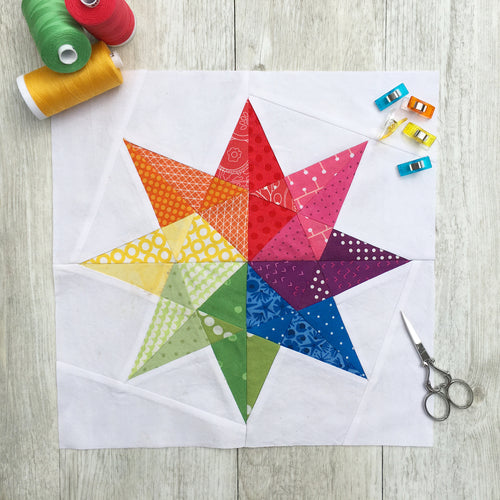 Rainbow Star Quilt Block Pattern by Penny Spool Quilts. Eight pointed star in rainbow colours on white background, with spools of thread, clips and small scissors on wood background.