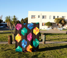 Load image into Gallery viewer, Facets quilt pattern by Penny Spool Quilts. Twin size quilt with large scale gemstones in pink, yellow, blue and green on black background, held up in front of house and palm trees.