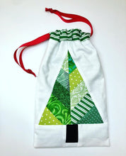 Load image into Gallery viewer, Festive Forest table runner and quilt block pattern by Penny Spool Quilts. Foundation paper pieced pattern. Image shows drawstring gift bag made from a single block in green on white, with red drawstring.