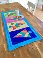 Load image into Gallery viewer, Festive Forest table runner and quilt block pattern by Penny Spool Quilts. Foundation paper pieced pattern. Image shows table runner in retro christmas colours of blue, orange, pink, green and yellow, on a table with glass of milk and cookies.