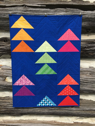 Flocks of Colour quilt pattern by Penny Spool Quilts. Baby quilt in rainbow flying geese on dark blue background, hanging on log wall.
