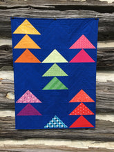 Load image into Gallery viewer, Flocks of Colour and Mini Flocks Pattern Bundle by Penny Spool Quilts. Flocks of Colour baby quilt with rainbow geese on dark blue background, on log wall.