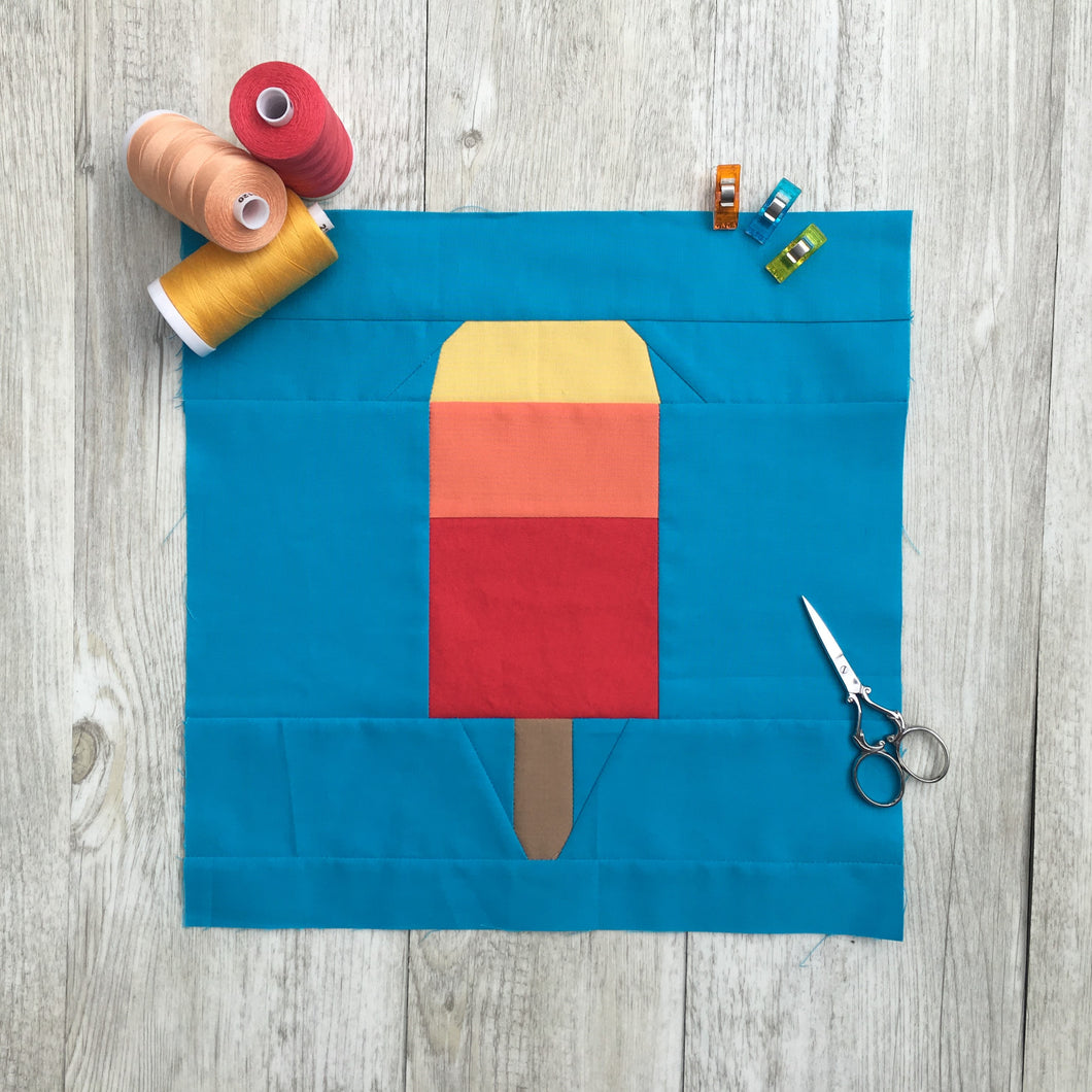 Popsicle 1 quilt block pattern by Penny Spool Quilts. Part of the Ice Cream Sunday collection. Tri-coloured popsicle in yellow, orange and red solid fabrics on blue background. shown with spools of thread, clips and small scissors