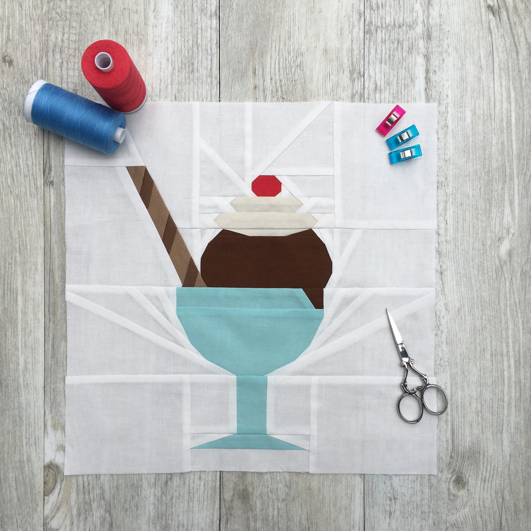 Ice Cream Bowl quilt block pattern by Penny Spool Quilts. Part of the Ice Cream Sunday collection. Sample shows chocolate ice cream topped with whipped cream and a red cherry, and a striped chocolate wafer straw, in a turquoise bowl with stem, on white background. Shown with spools of thread, pins and small scissors
