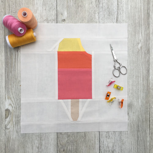 Popsicle 2 quilt block pattern by Penny Spool Quilts. Part of the Ice Cream Sunday collection. Tri-coloured popsicle with a bite taken out in top right corner, in yellow, orange and pink solid fabrics on white background. shown with spools of thread, clips and scissors