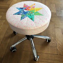 Load image into Gallery viewer, Rainbow Star Quilt Block Pattern by Penny Spool Quilts. Eight pointed star made using a rainbow of Tula Pink fabrics and used as a cover for wheeled office stool. Picture shows office stool from the side.