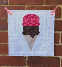 Load image into Gallery viewer, Ice Cream Cone quilt block pattern by Penny Spool Quilts. Part of the Ice Cream Sunday collection. Wafer cone with one scoop of chocolate ice cream and one scoop of pink ice cream, on white background. Shown on red brick wall
