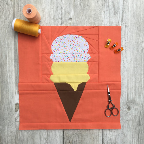 Ice Cream Cone quilt block pattern by Penny Spool Quilts. Part of the Ice Cream Sunday collection. Chocolate wafer cone with one scoop of yellow ice cream and one scoop of rainbow sprinkled ice cream, on orange background.