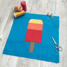 Load image into Gallery viewer, Popsicle 1 quilt block pattern by Penny Spool Quilts. Part of the Ice Cream Sunday collection. Tri-coloured popsicle in yellow, orange and red solid fabrics on blue background. shown with spools of thread, clips and scissors