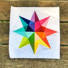 Load image into Gallery viewer, Rainbow Star Quilt Block Pattern by Penny Spool Quilts. Eight pointed star in rainbow solid fabrics on white background, shown on wood floor.
