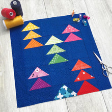 Load image into Gallery viewer, Flocks of Colour and Mini Flocks Pattern Bundle by Penny Spool Quilts. Mini Flocks quilt block with rainbow geese on dark blue background, on light grey floor with spools of thread, quilting clips and small scissors.  foundation paper piecing.