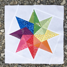 Load image into Gallery viewer, Rainbow Star Quilt Block Pattern by Penny Spool Quilts. Eight pointed star in rainbow print fabrics on white background, on gravel.